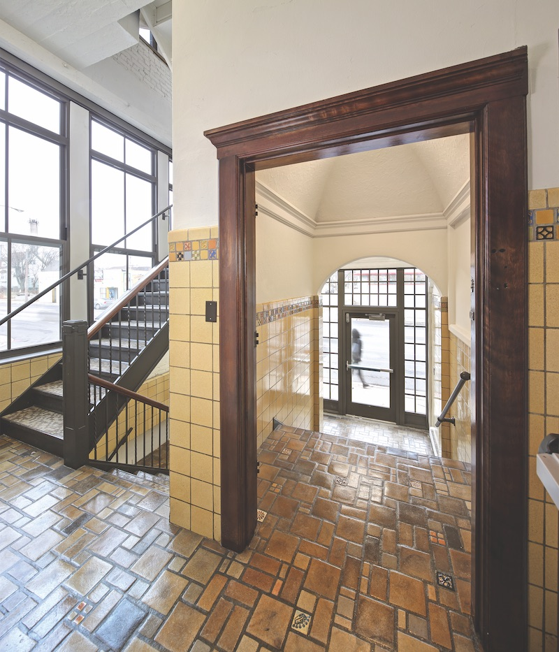 The entry vestibule and stairs with period floor tiles and wainscoting
