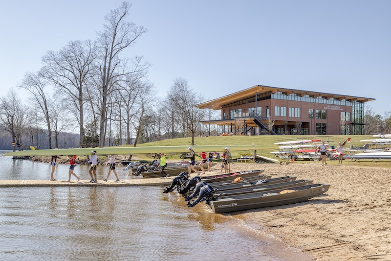 People carrying a boat in front of the Clemson's Outdoor Education Center
