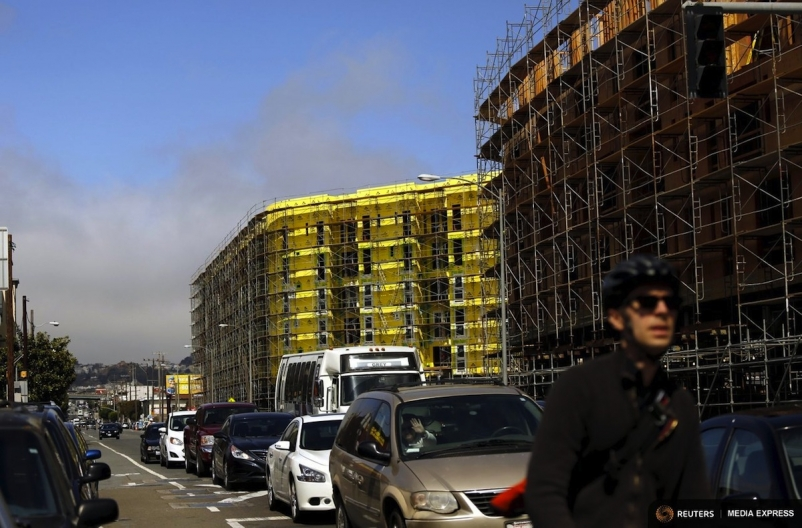 A bicyclist sits in traffic near a housing construction project in San Francisco. Photo: Reuters/Robert Galbraith
