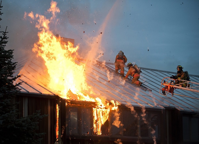 Firefighters on the roof of a burning building in Alaska