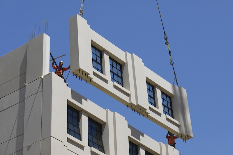 An exterior wall panel, manufactured by Clark Pacific, is positioned into place. Image: Clark Pacific