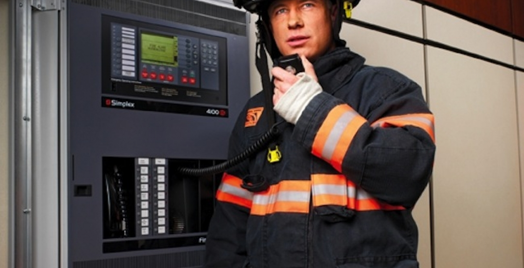 A firefighter uses the voice capabilities of a fire alarm panel (in this case, a