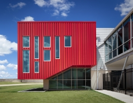 PAC-CLAD Highline S1 metal wall panel system clads Del Valle Career & Tech Center in 3 shades of red