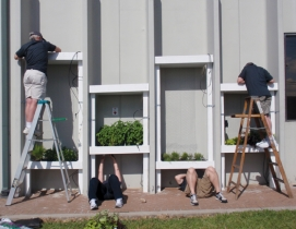 HMC volunteers install planters in a vertical garden wall at the Second Harvest